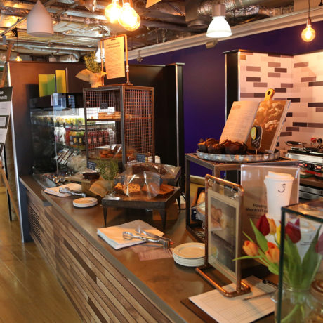A dark wood coffee bar filled with shelves of healthy food