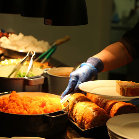 A close up shot of food and a hand serving from the heated serving area